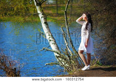 Brooding long-haired charming brunette girl stands next to a birch tree by the lake.