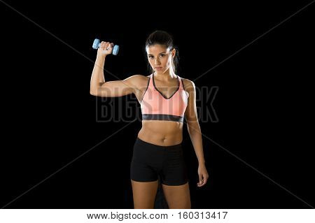 young attractive hispanic sport woman posing in fierce and badass face expression holding dumbbell hand weight isolated on black background in healthy lifestyle and fitness concept