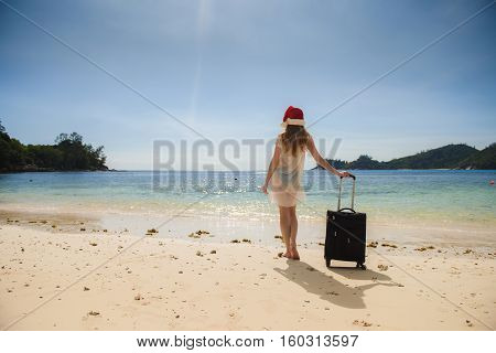 Christmas Vacation. Young woman with a red Santa Claus hat and suitcase on the beach. Transparent clothes, bathing suit.