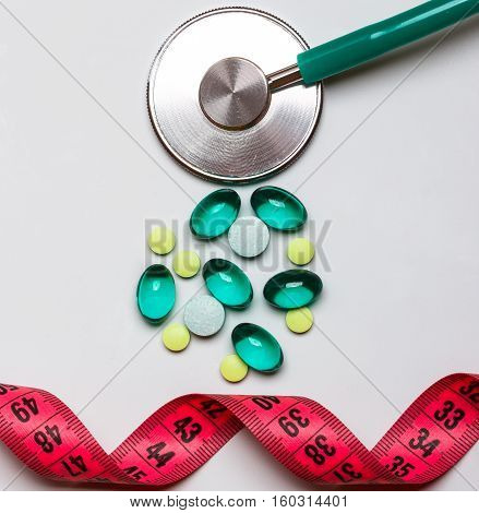 Healthy eating medicine health care food supplements and weight loss concept. Pills with measuring tape and stethoscope on table