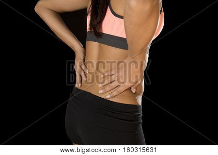 young attractive hispanic fitness woman touching and grabbing her lower back suffering back pain isolated on black background in sport injury and body health care concept
