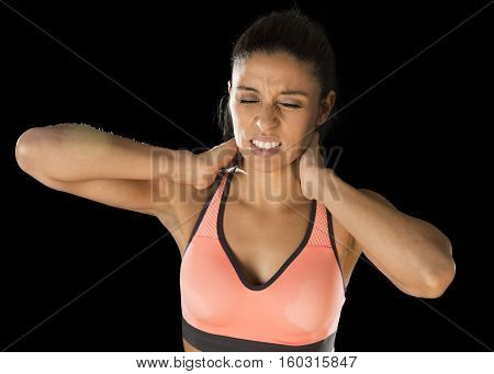 young attractive hispanic fitness woman touching and grabbing her neck and upper back suffering cervical pain isolated on black background in sport injury and body health care concept