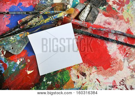 artist's palette with colored inks deposited randomly and blank card