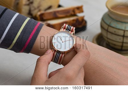 Girl's hand with wrist watches at the coffee break in front of hot chocolate and cake