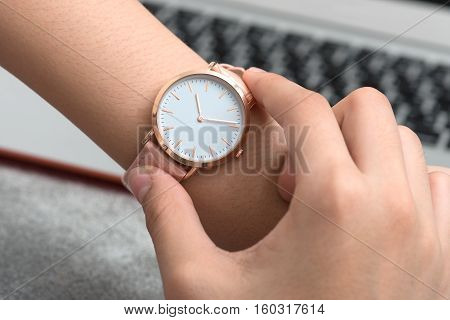 Girl's hand with wrist watch in front of desk with notebook computer