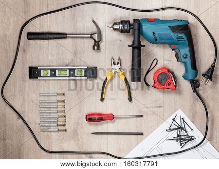 Set of construction tools to repair on a wooden surface: drill, hammer, pliers, self-tapping screws, roulette, construction level, drawing, construction pencil. Top view
