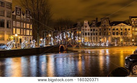 AMSTERDAM - DEC 29, 2015: Tour boats decorate the canals with light trails as they are cruising the exhibition boat route