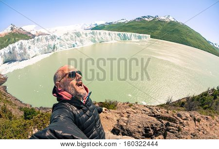 Young man solo traveler taking selfie at Perito Moreno glaciar in south american argentinian Patagonia - Adventure wanderlust concept on world famous nature wonder in Argentina - Warm turquoise filter
