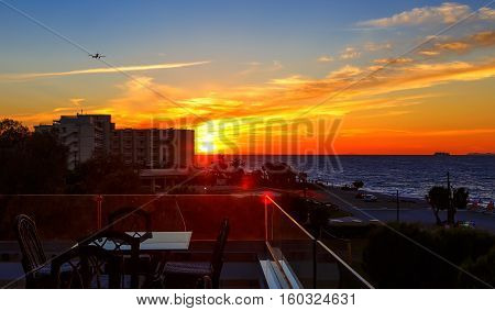 sunset over the sea with views from the balcony caf , a passing plane and ship. Greece