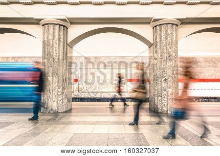 People walking on generic platform of underground subway metro station - Urban public transportation concept with passengers commuting at rush hour working time - Defocused motion blur composition