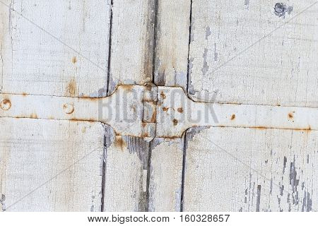 Old door from darkened boards with archaic iron plates