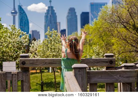 little girl playing, standing at kids play ground and stretched her arms toward Toronto city skyscrapers on sunny day