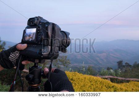 Details of professional landscape photographer adjusts dslr camera on hand.