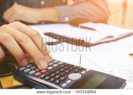 Close up man using calculator in home office.