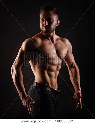 Bodybuilder posing on a black background. Dramatic portrait of an athlete. Drying. Relief and sculptural muscles of the body. Healthy lifestyle concept. The abdominal muscles and shoulders.