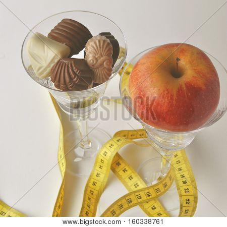 Chocolates and an apple in champagne glasses with measuring tape - new year's resolutions for weight loss and healthy lifestyle