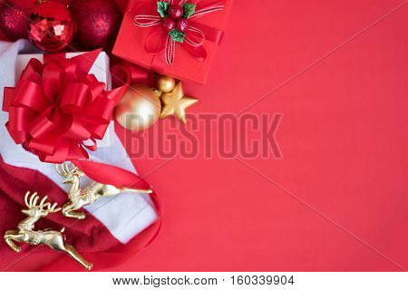 Christmas background decorations gift boxes inside santa claus hat with two gold reindeer and red ribbon bow with ornament bauble on red backdrop with copy space still life style Greeting card for new year