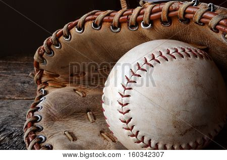 A close up image of an old used baseball and baseball glove.