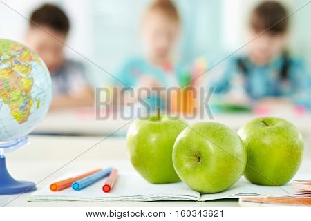 Group of granny smith apples and other school objects on desk in classroom