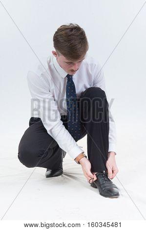 Business Man Tying Shoe On White Background