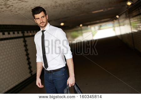 Handsome young businessman walking in underpass, looking away.