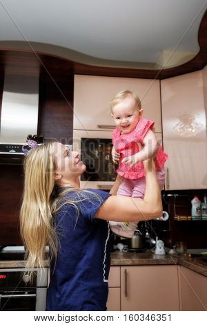 mother playing with baby in the kitchen
