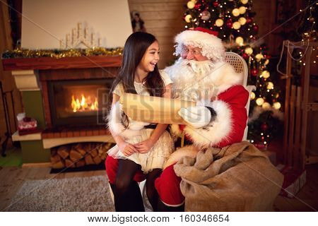 Santa Clause with young girl in lap reading Christmas whishes from long paper
