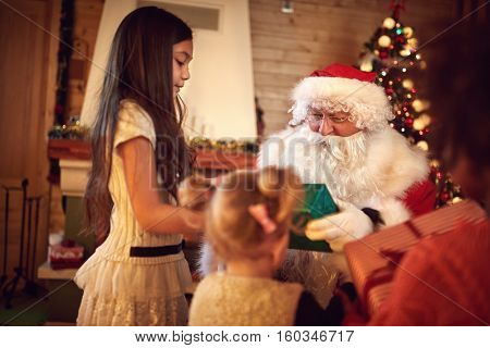 Santa Claus giving Christmas gifts to eagerly waiting children