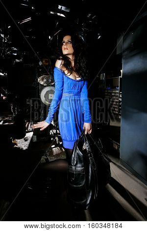 Brunette model with a blue dress and black tights posing with a bag in an old and a dark factory with a strange look on face like looking at something