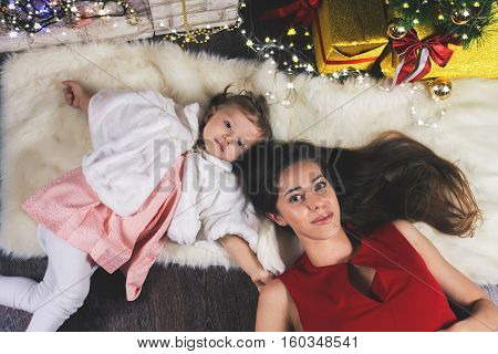 Cute baby and happy mum near Christmas tree. New Year 2017. Fairy tale. Mothercare is most important in children life. Baby and daughter