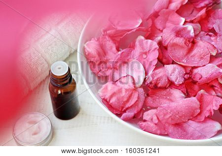 Aromatherapy body treatment, warm herbal bath soak. Bowl of Rose petals, essential oil, complimentary emollient sample. Luxury natural skincare line.  Framed natural pink flower blur.