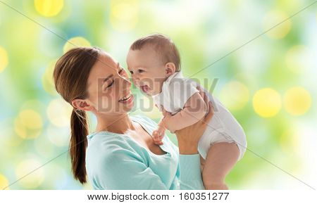 family, motherhood, child and parenthood concept - happy smiling young mother with little baby over green lights background