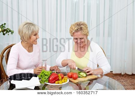 Two smiling mature women sitting at the table and cutting vegetables