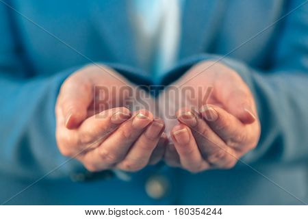 Businesswoman with open palms of her hands asking for something
