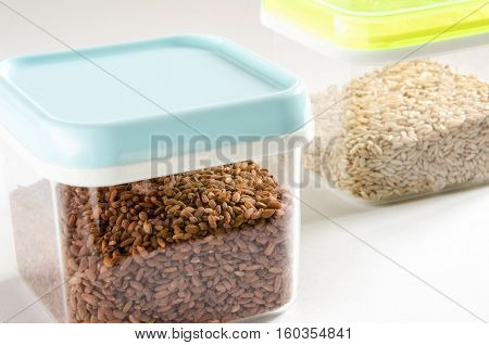 Food storage. Food ingredients (brown rice and wild rice) in plastic containers. Selective focus.