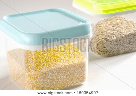 Food storage. Food ingredients (polenta and wild rice) in plastic containers. Selective focus.