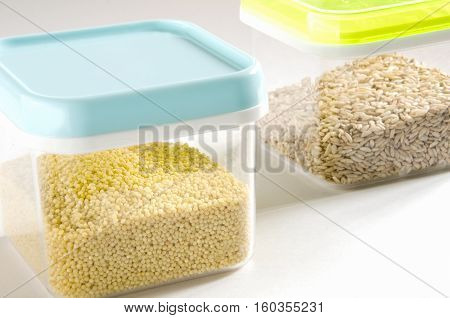 Food storage. Food ingredients (millet and wild rice) in plastic containers. Selective focus.