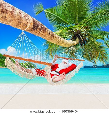 Santa Claus sunbathe in white cozy mesh hammock under coconut palm tree at tropical sandy ocean island beach - Happy New Year and Merry Christmas travel destinations concept