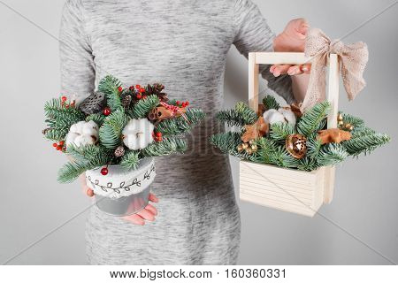 young woman holding christmas compositionin hands in light, seasonal holidays, rustic theme, adorning.