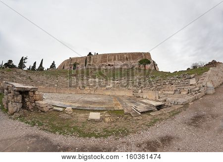 Ancient stone wall on top of the mountain and the amphitheater at the bottom. Photo fish-eye.