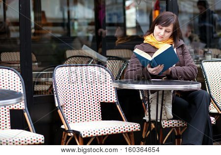 Beautiful Young Girl Reading A Book In Parisian Street Cafe
