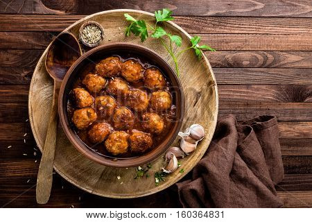 meatballs in tomato sauce on wooden background, italian cuisine
