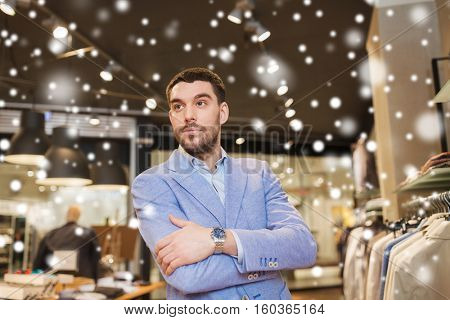 sale, shopping, fashion, style and people concept - happy young man or businessman in jacket and wristwatch at clothing store over snow