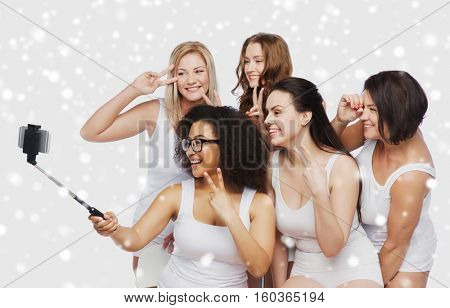 technology, friendship, body positive and people concept - group of happy women in white underwear taking picture with smartphoone on selfie stick over snow