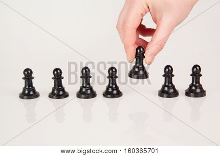 a hand taking pawn from the row