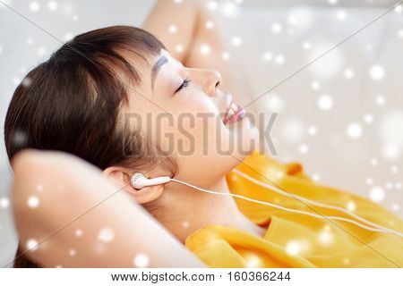 people, technology, relax and leisure concept - happy asian young woman lying on sofa with earphones listening to music at home over snow