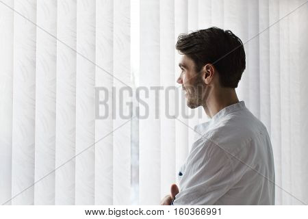 A man stands in a half turn and smiling against the window