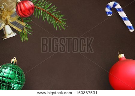 Christmas fir branch red wavy dull green ribbed ball bell and stick on a dark background