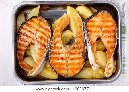 Grilled salmon steak with potatoes. Top view.