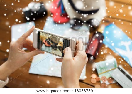 winter holidays, tourism, travel, technology and people concept - woman with smartphone photographing map and beach stuff